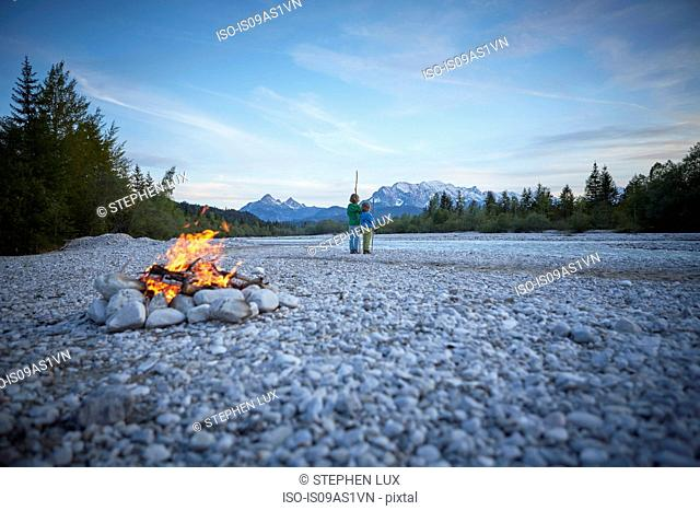 Rear view of boys near campfire holding sticks, Wallgau, Bavaria, Germany