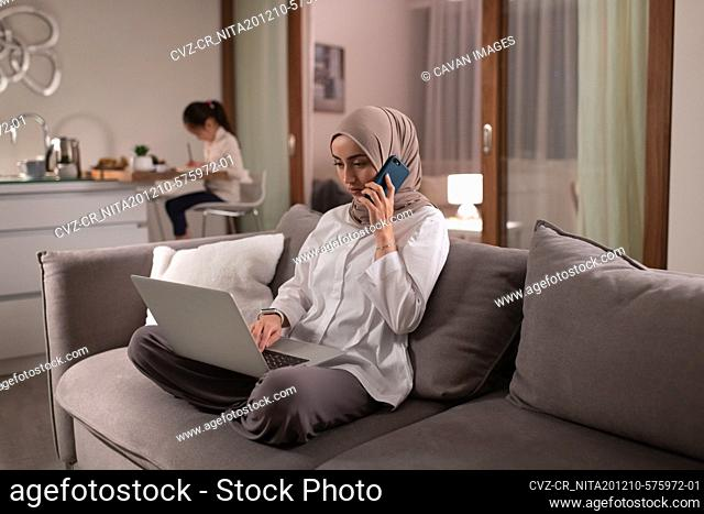 Muslim mother working at home