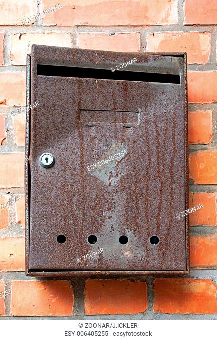 An old and rusty postbox in front of a red brickwa