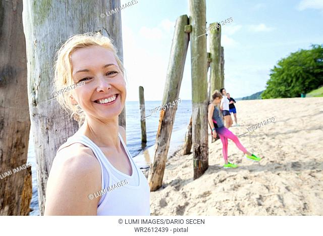 Young woman and friends on beach taking a break