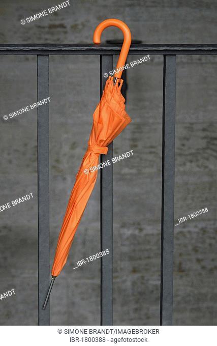 Orange umbrella on railing