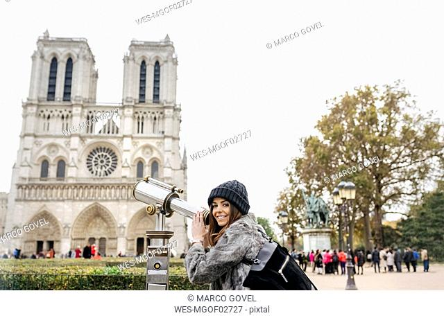 France, Paris, tourist using telescope in front of Notre Dame