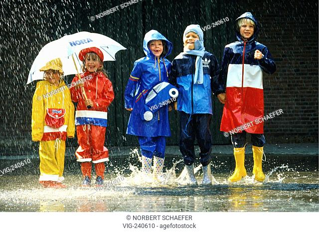 5 children in the age of 4-8 years are standing at the roadside in the middle of a puddle wearing coulered raincoats  - 0, GERMANY, 08/08/2002