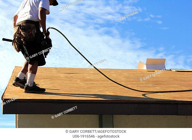 a man or roofer using a nail gun and working to replace the plywood or wood or covering and shingles on a house roof