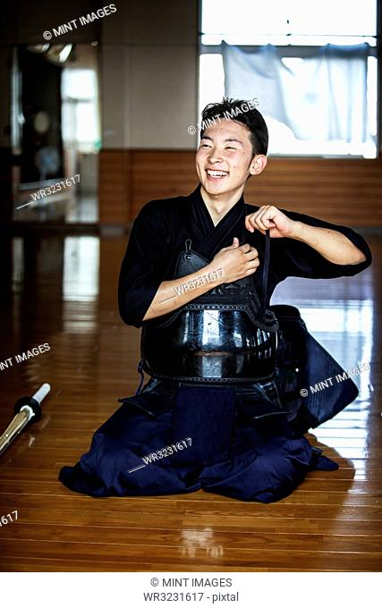 Male Japanese Kendo fighter kneeling on floor, fastening his breastplate