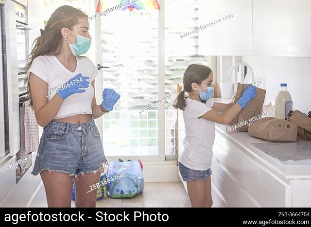 mother and daugther organizing the groceries they just brought