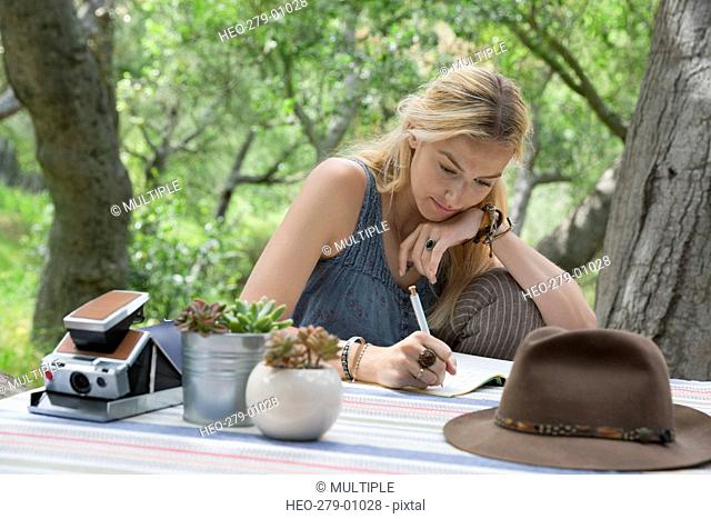 Young woman writing in journal at patio table