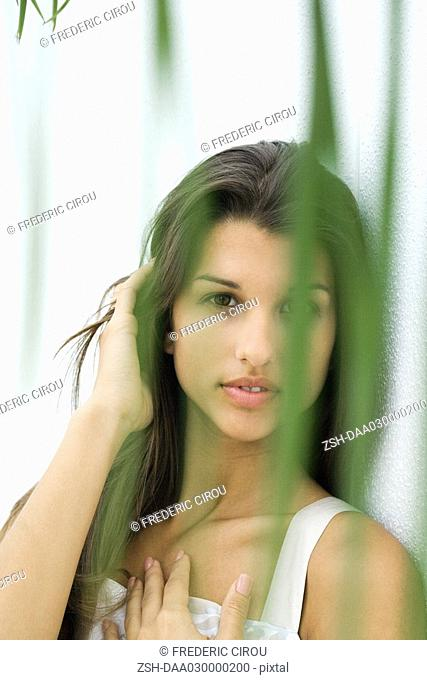 Teen girl looking at camera through foliage, hand on chest