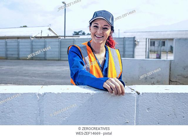 Portrait of smiling young woman wearing overalls and reflective jacket