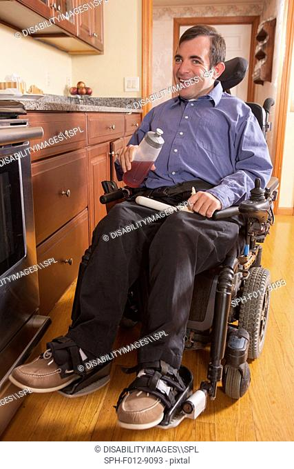 Man with Cerebral Palsy in home kitchen having his lunch