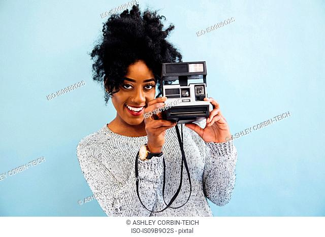 Woman with instant camera looking at camera smiling