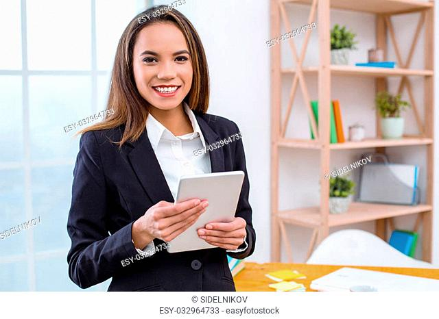 Beautiful young business woman in modern office with big window. Woman smiling, using tablet computer and looking at camera