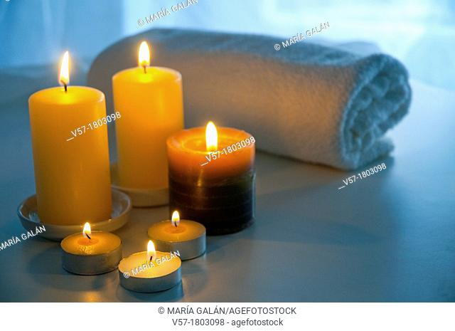 Lit up candles and towel