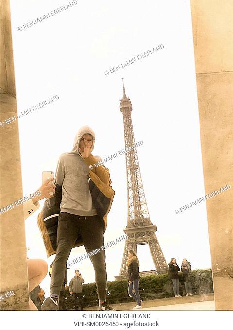 young Millennial tourist man photographed through mirror next to touristic sight Eiffel Tower, Tour Eiffel, at Espl. du Trocadéro, in Paris, France