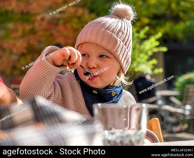 Portrait of toddler girl eating at outdoor cafe in autumn