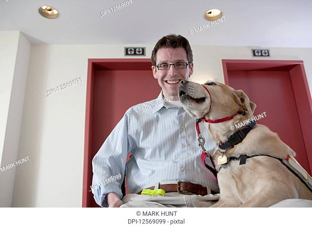 Man with a Spinal Cord Injury playing with a service dog at the elevator
