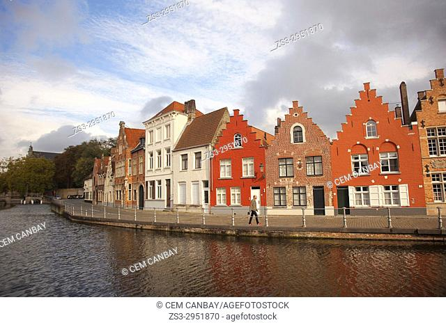 Man walking in front of the colorful traditional houses by the canal in the city centre, Bruges, West Flanders, Belgium, Europe