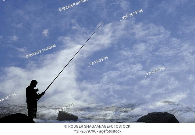 Lone fisherman with rod in hand, at the seaside, Cape Town, South Africa
