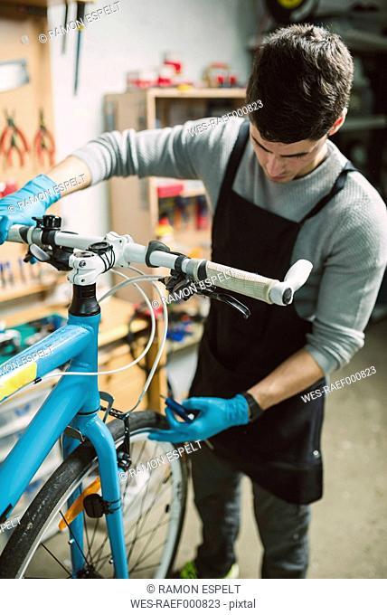 Mechanic repairing a bicycle in his workshop