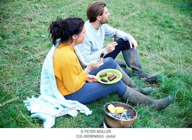 Couple sitting in rural field having barbecue