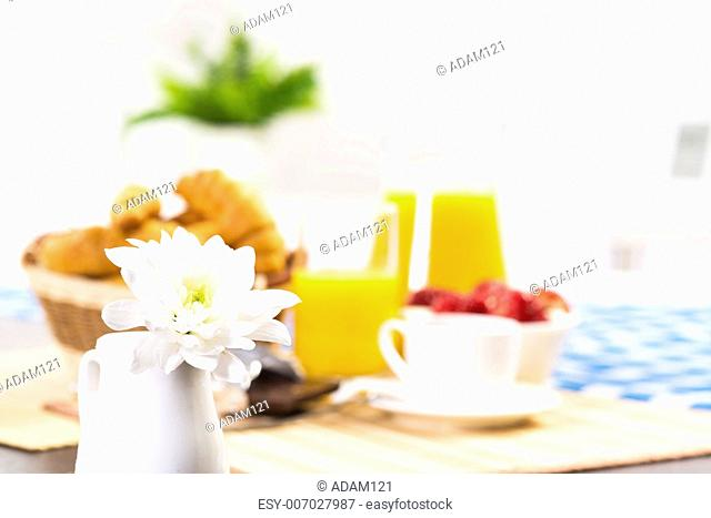 white flowers in a jug in the background covered with a breakfast table
