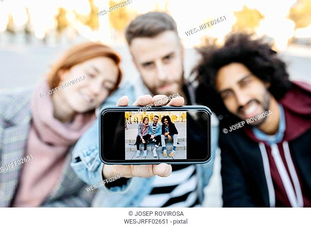 Three friends showing a selfie on camera phone