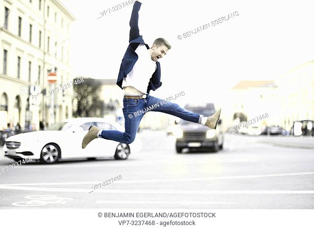 lively young man jumping at street in city, wearing business blazer and jeans, powerful, in Munich, Germany