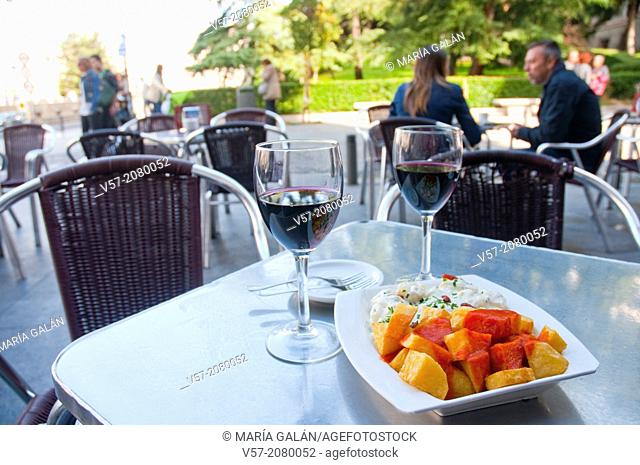 Spanish appetizer: bravas potatoes, alioli potatoes and two glasses of red wine in a terrace. Madrid, Spain
