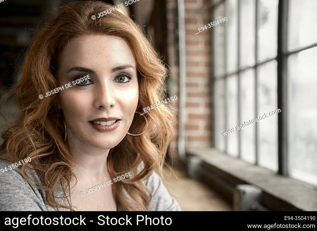 A portrait of a pretty 37 year old redheaded woman smiling directly at the camera