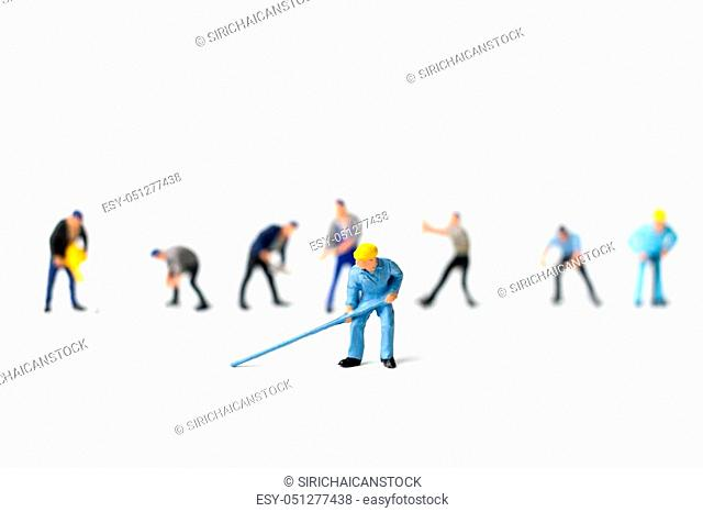Miniature people worker holding tool on white background, construction concept