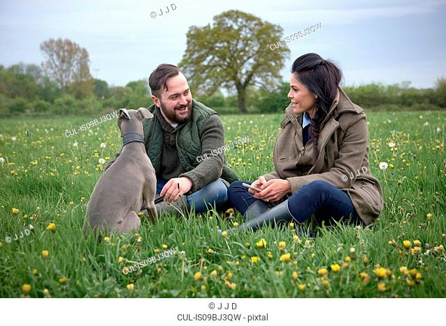 Woman and man sitting in field with dog