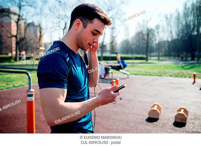 Calisthenics at outdoor gym, young man listening to earphone and looking at smartphone