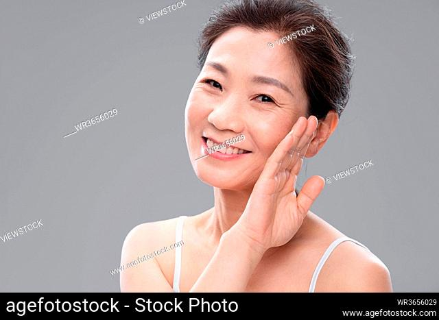Elegant middle-aged woman touch the cheek with the back of hand