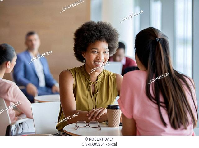 Smiling businesswomen enjoying coffee break