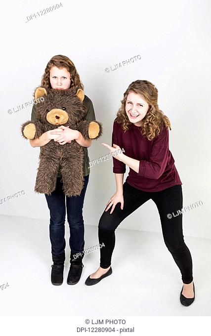 Studio shot of one friend making fun of another friend holding her teddy bear; Alberta, Canada