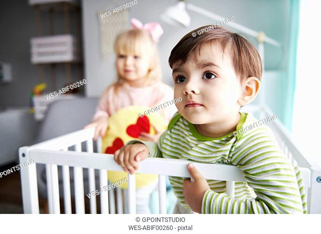 Portrait of toddler in crib with his sister in the background