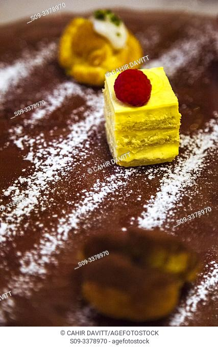Italian Dolce desert dish comprising selection of mini cakes served with a chocolate and icing sugar powder, Ghetto Ebraico, Bologna, Emilia Romanga, Italy