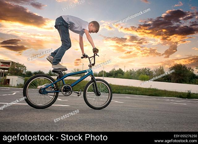 Young fearless boy doing spectacular and dangerous tricks on bike, standing on the saddle with both legs