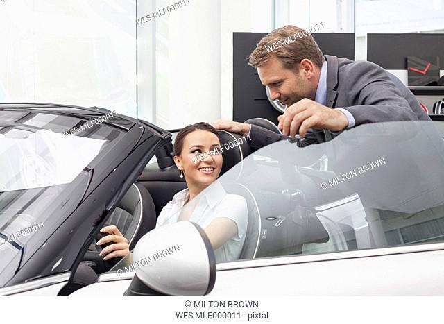 At the car dealer, Salesman talking to client at convertible car