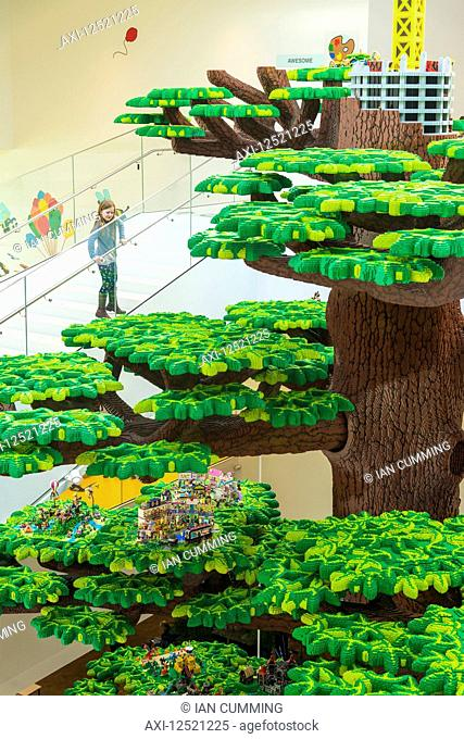 Girl looking over giant Lego tree in the Lego House; Billund, Denmark