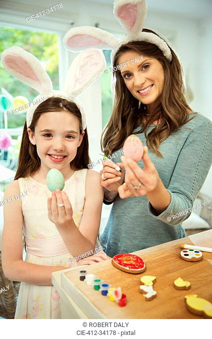 Portrait smiling mother and daughter wearing costume rabbit ears showing decorated Easter eggs