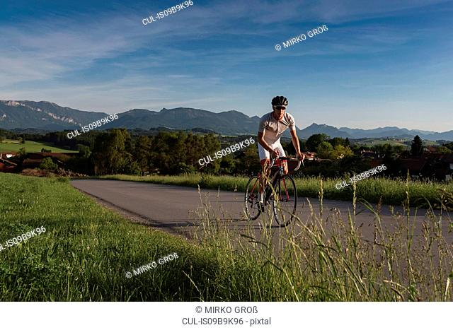 Young male cyclist cycling up rural road