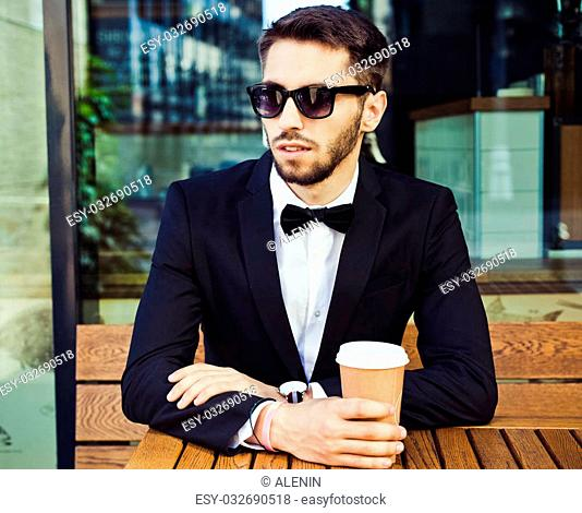 Coffee break. Man business man in a business suit and a glass of coffee in a city cafe, business centers, office building. Summer. Warm tone. Close up