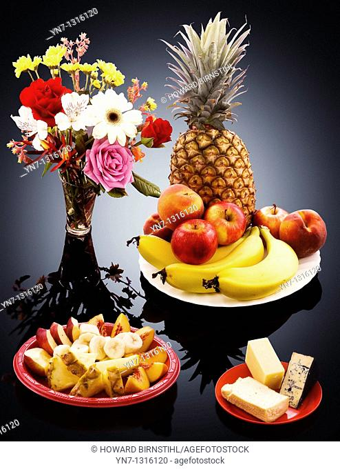 studio image of platters of fruit,cheese,and flowers on a glowing background