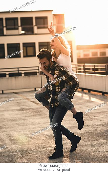 Happy young man giving his girlfriend a piggyback ride on roof terrace at sunset