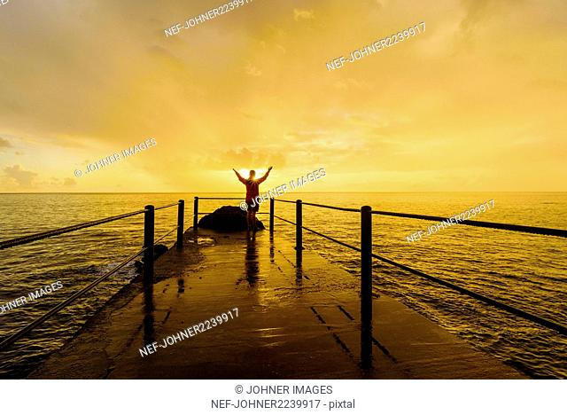 Person on jetty at sunset