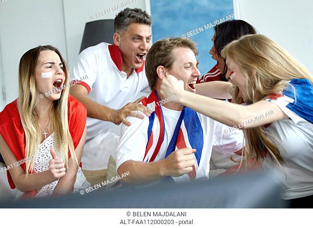 British football fans celebrating victory while watching match on TV