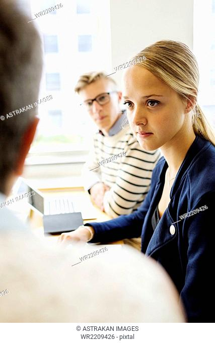 Female student sitting with teacher and friend in classroom
