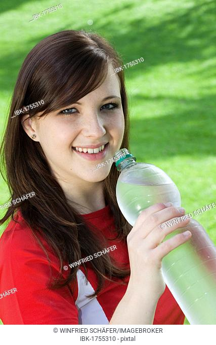 Young woman in sportswear with a bottle of water in her hand