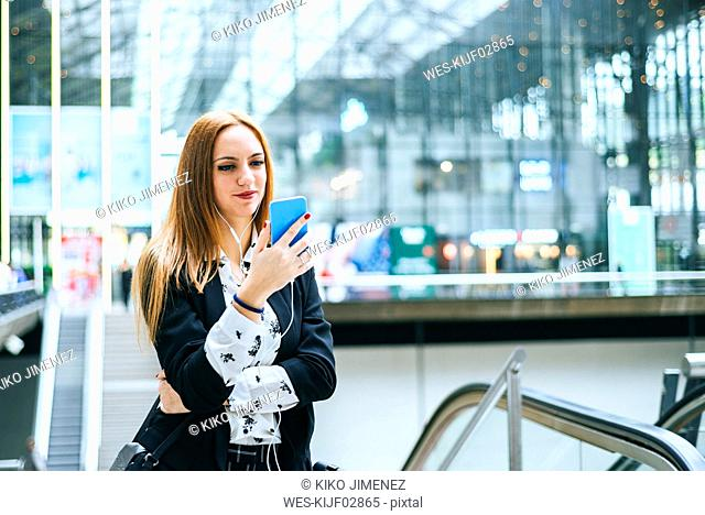 Young woman with earphones and cell phone at train station
